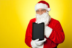 Santa Claus holding newly launched tablet device Royalty Free Stock Photography