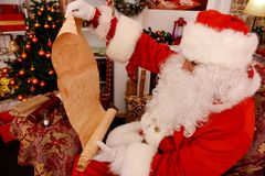 Santa Claus holding old scroll of parchment, stock image