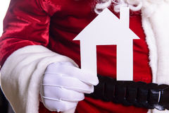 Santa Claus holding paper house Royalty Free Stock Photos