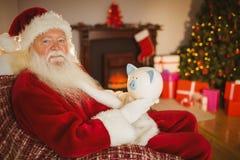 Santa claus holding piggy bank Royalty Free Stock Photo