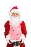 Santa Claus holding a piggybank. Isolated on white background Royalty Free Stock Image