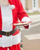 Santa Claus Holding Plate With Cookies Stock Photo