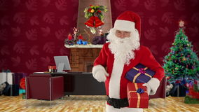 Santa Claus holding presents in his modern Christmas Office, stock footage Royalty Free Stock Photography