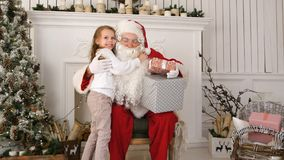 Santa Claus holding presents and hugging a little cute girl. Professional shot on Lumix GH4 in 4K resolution. You can use it e.g. in your commercial video Stock Images