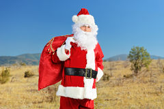 Santa Claus holding presents outdoors Royalty Free Stock Images