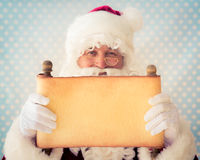 Santa Claus holding scroll paper blank Royalty Free Stock Photo