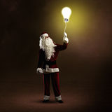 Santa Claus is holding a shining lamp Stock Photography