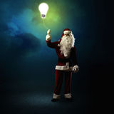 Santa Claus is holding a shining lamp Royalty Free Stock Photography