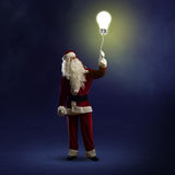 Santa Claus is holding a shining lamp Royalty Free Stock Image
