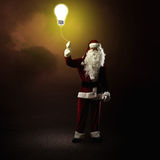 Santa Claus is holding a shining lamp Royalty Free Stock Images