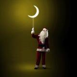 Santa Claus holding a shining moon Royalty Free Stock Images