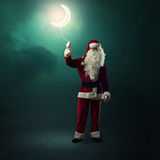 Santa Claus holding a shining moon Stock Photo