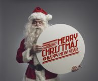 Santa Claus holding a sign with Christmas wishes. Santa Claus holding a round sign with Christmas wishes and smiling at camera royalty free stock photography