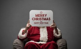 Santa Claus holding a sign. Santa Claus sitting on an armchair and holding a Christmas Card Stock Image