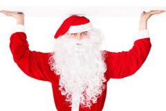 Santa Claus holding something over head Royalty Free Stock Images