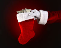 Santa Claus Holding a Stocking Full of Cash. Closeup of Santa Claus holding a stocking full of cash. Only Santa's hand and arm over a light to dark red Stock Image