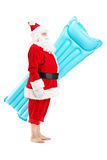 Santa claus holding a swimming mattress on vacation. Full length portrait of a Santa claus holding a swimming mattress on vacation, isolated on white background Royalty Free Stock Photo