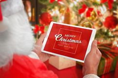 Santa Claus holding tablet with Merry Christmas greeting massage. Christmas tree with gifts, lights and decorations in background Royalty Free Stock Photos