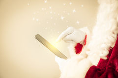 Santa Claus holding tablet PC Stock Photo