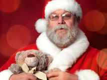 Santa Claus holding teddy bear stock image