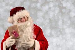 Santa Claus Holding um presente de Natal Foto de Stock