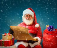 Santa Claus holding vintage paper and reads long list of gifts for children. Royalty Free Stock Photography