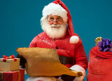 Santa Claus holding vintage roll and reads a long listof gifts for children. Stock Photos