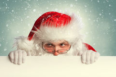 Santa Claus holding white blank banner. Looking around Royalty Free Stock Images