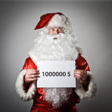 Santa Claus is holding a white paper in his hands. One million d. Ollars concept Royalty Free Stock Photos