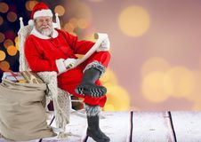 Santa claus holding wish list with sack of gifts Stock Photos