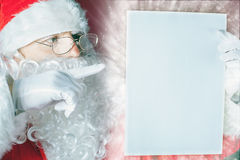 Santa Claus holding a wishlist, white letter or paper. Royalty Free Stock Photography