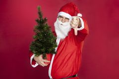 Santa Claus holds a Christmas tree and shows thumbs down Stock Image
