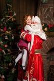 Santa Claus holds on hands happy little girl. Christmas scene Stock Image