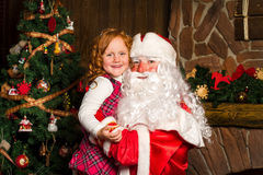 Santa Claus holds on hands happy little girl. Royalty Free Stock Image