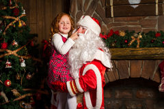 Santa Claus holds on hands happy little girl. Christmas scene Stock Photography