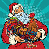 Santa Claus holds in his hands the cock. Pop art retro vector. The symbol of the new year Stock Photos