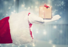 Santa Claus holidng a small Christmas present Stock Photos