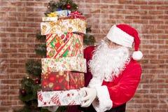 Santa Claus holt Weihnachtsgeschenke Stockfotografie
