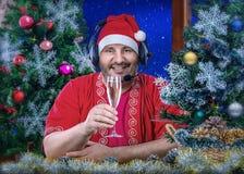 Santa Claus in hoofdtelefoons die een Gelukkig Nieuwjaar roosteren royalty-vrije stock fotografie