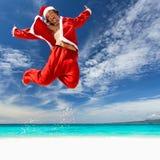 Santa Claus hoppar på den tropiska stranden Arkivbilder