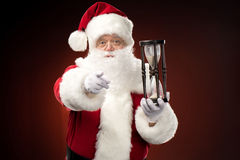 Santa Claus with hourglass pointing at camera Stock Images