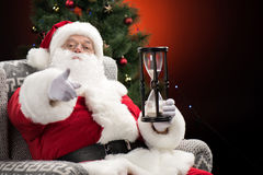 Santa Claus with hourglass  pointing at camera Royalty Free Stock Photography
