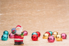 Santa Claus with Сhristmas balls. On illuminated background Royalty Free Stock Photography