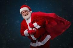 Santa Claus with huge sack. Portrait of happy Santa Claus with a huge sack stock image