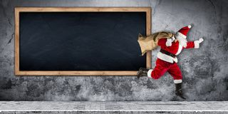 Santa claus in a hurry with bag full of presents running jumping stock photography