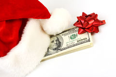 Santa Claus-Hut und Stapel des Geldamerikaners hundert Dollarscheine mit rotem Bogen Lizenzfreie Stockfotografie