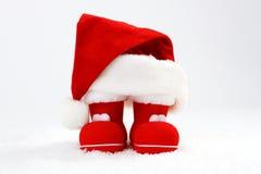 Santa Claus-Hut und -stiefel auf Schnee vor weißem Hintergrund Lizenzfreies Stockfoto