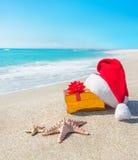 Santa Claus-Hut und Weihnachtsgeschenkbox auf der Küste mit Meer Lizenzfreie Stockfotos