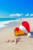 Santa Claus-Hut und Weihnachtsgeschenkbox auf der Küste mit Meer Lizenzfreies Stockfoto