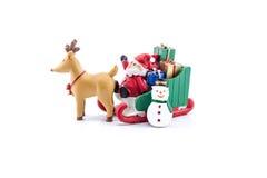 Santa Claus, i att bära för släde gåvor med renen och snögubben Arkivfoto